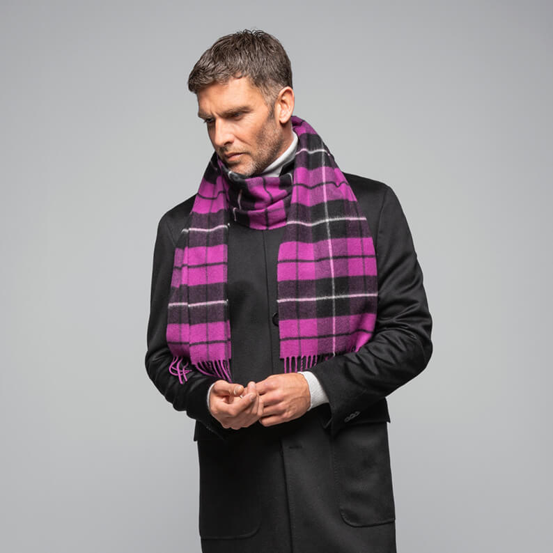 Model wearing an oversized cashmere scarf in Caledonian Forest tartan