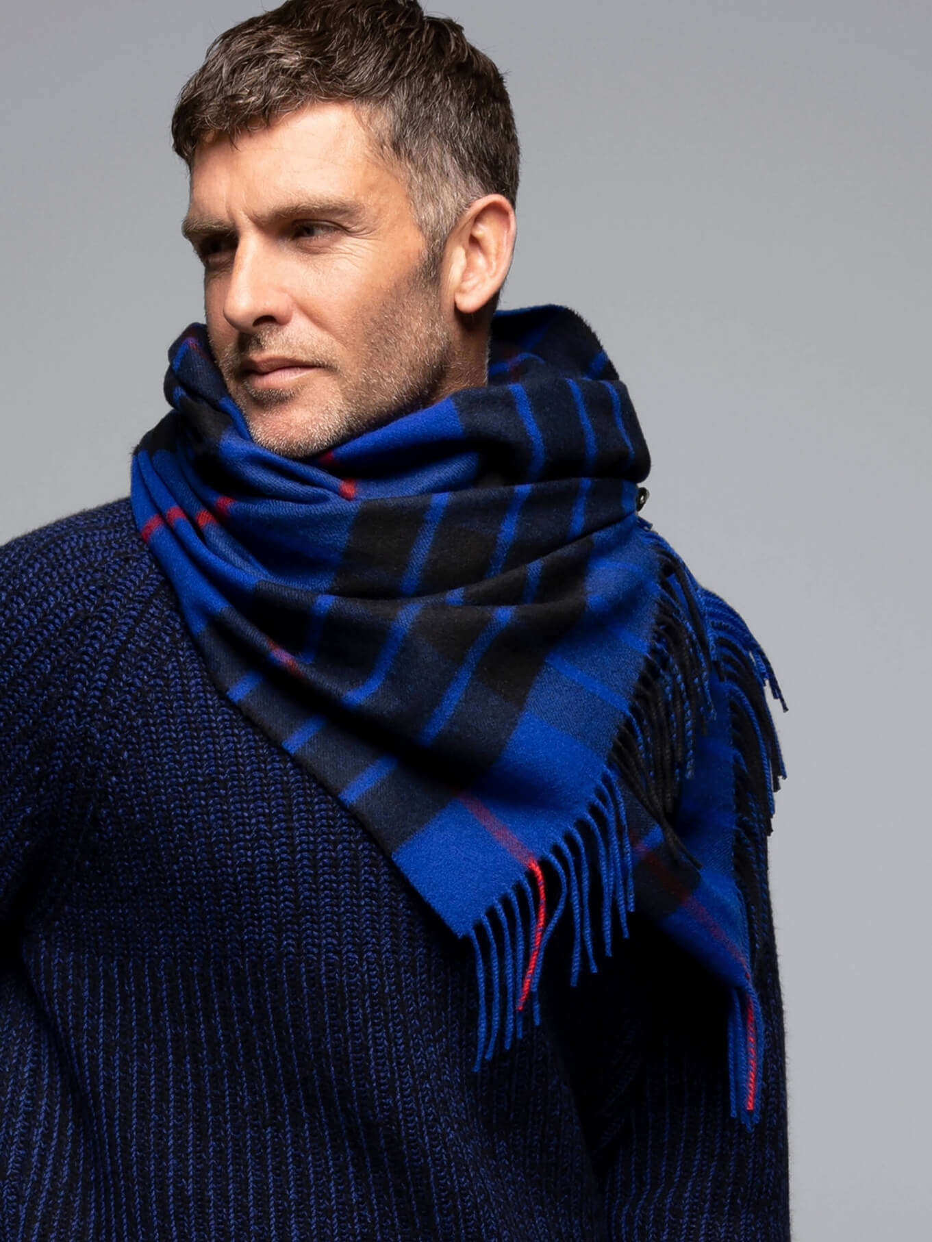 Johnstons of Elgin model wearing a Classic Tartan Cashmere Stole in Burn of Tynet, on a grey background