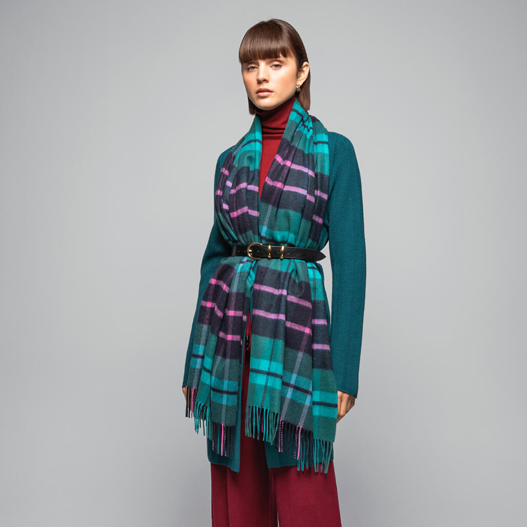 Johnstons of Elgin model wearing a Classic Tartan Cashmere Stole in Pluscarden Abbey, on a grey background