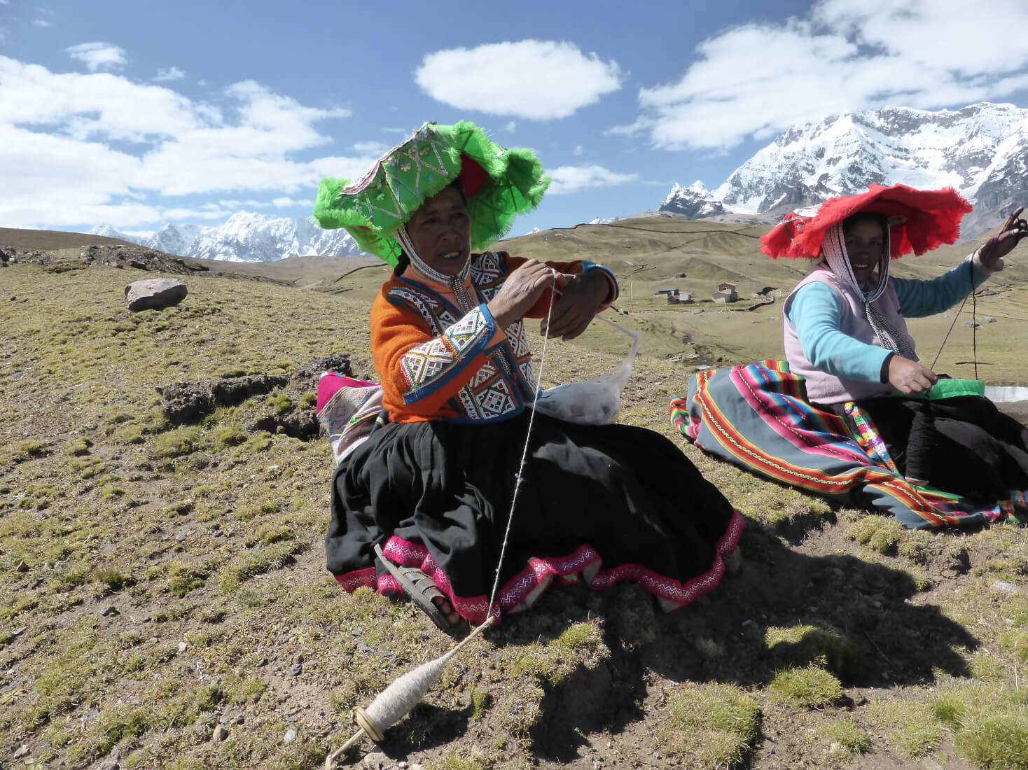 Two Peruvian women deftly spinning yarn by hand from wool fleece whilst taking a rest from walking. Snow capped Peruvian Andes in the distance.
