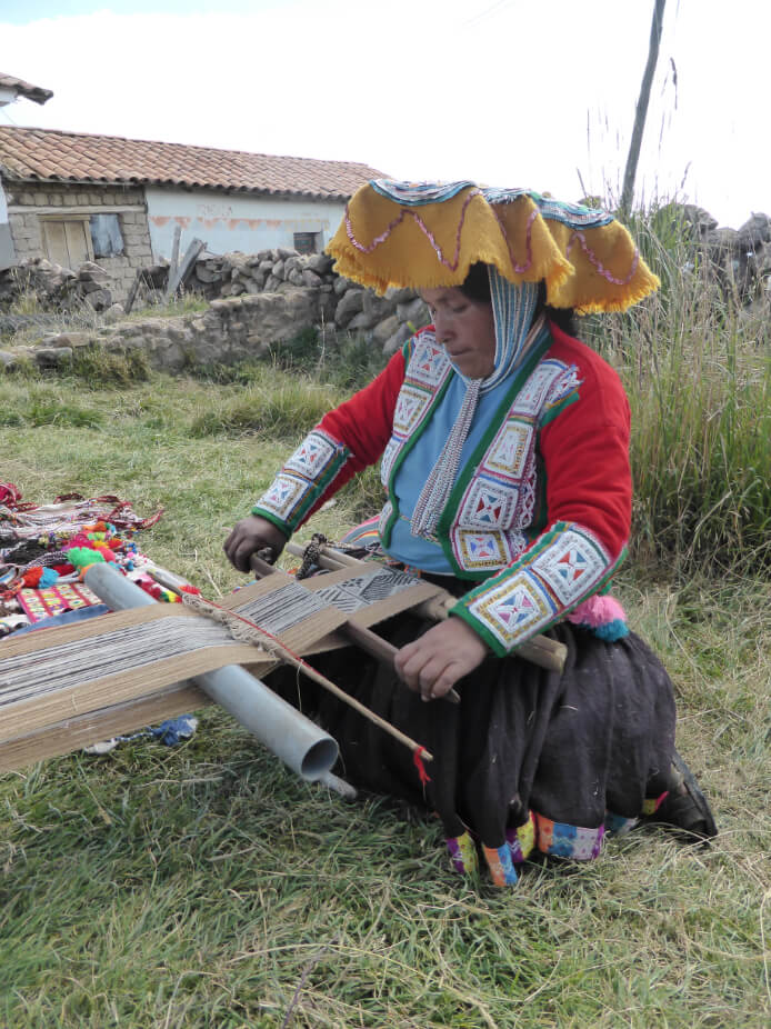 Peruvian woman weaving a complex fabric pattern by hand from memory.