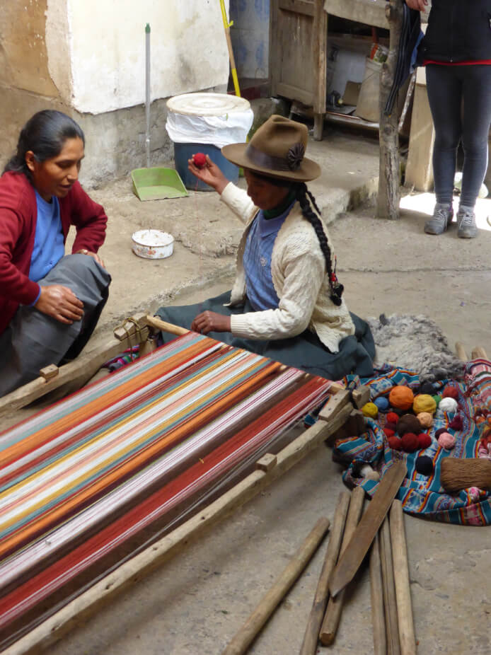 Two Peruvian women designing and making a warp in preparation for weaving.