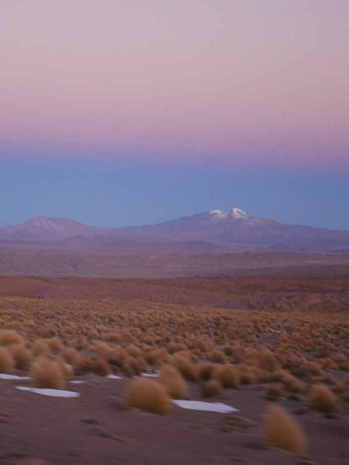 Landscape of mountains and flat grassy plains of the 'Altiplano' (high plain) of Southern Bolivia at twilight with soft shades of pink, blue and ochre blending together.