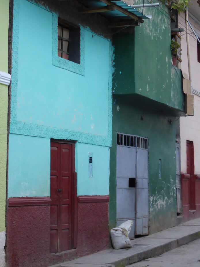 Painted buildings in Colombia combining dark burgundy, bright turquoise, dark green and soft grey/blue.