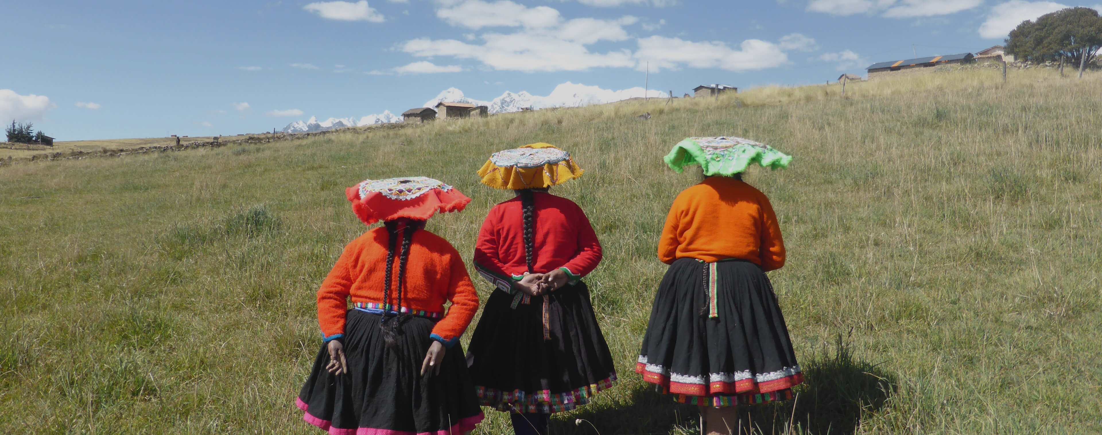 Three Peruvian women in traditional dress, walking across pasture with small dwellings and snow capped Peruvian Andes in the distance.