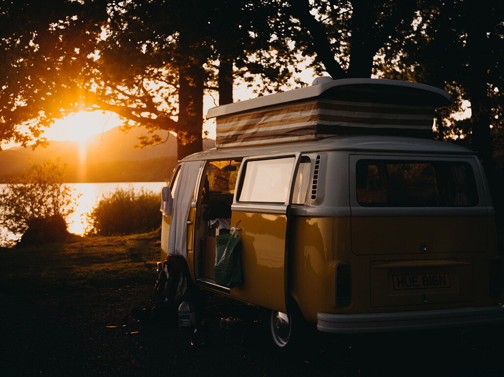 a camper van with the sunsetting in the distance