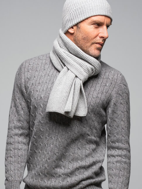 Johnstons of Elgin male model wearing cashmere jumper, scarf, and hat