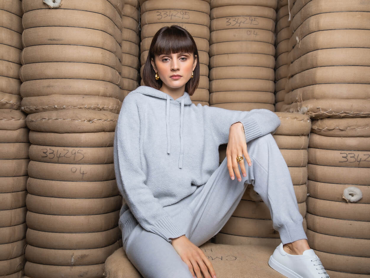 model wearing cashmere sitting on bales of cashmere